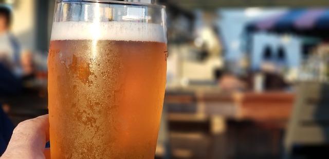 Ruka držící orosenou sklenici piva
