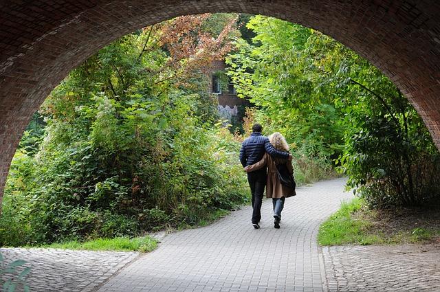 Dvojice držící se kolem ramen, na procházce v parku